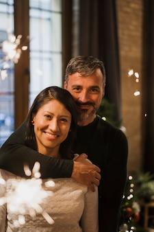 В любви пожилая пара обнимается с огненными блестками