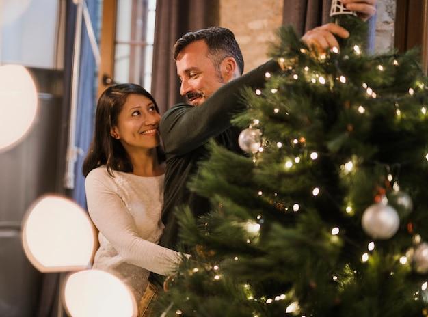 クリスマスツリーを飾る愛情の年配のカップル