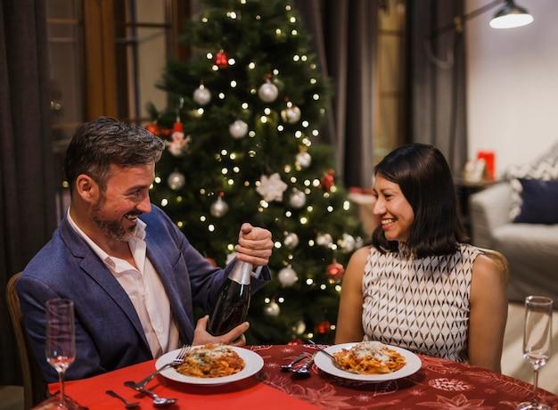 クリスマスディナーを一緒に持っている年配のカップル