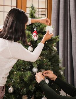 クリスマスツリーを一緒に飾る年配のカップル