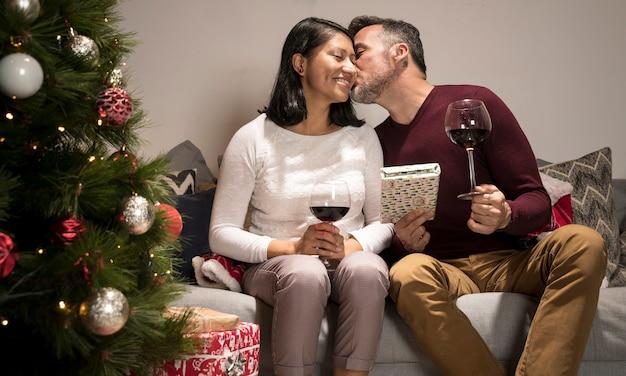 Мужчина целует женщину на рождество