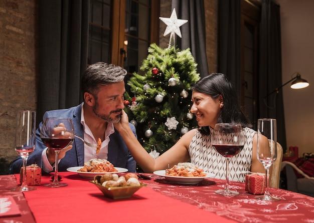 クリスマスディナーを持っているかわいいカップル