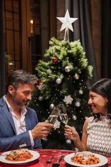 クリスマスディナーを祝う年配のカップル