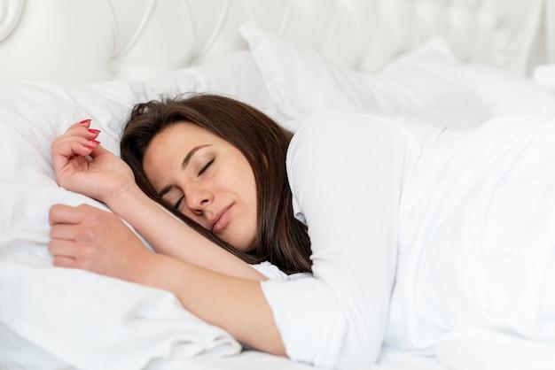 Среднего роста девушка спит в удобной кровати