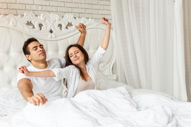 Средний снимок счастливая пара растягивается вместе