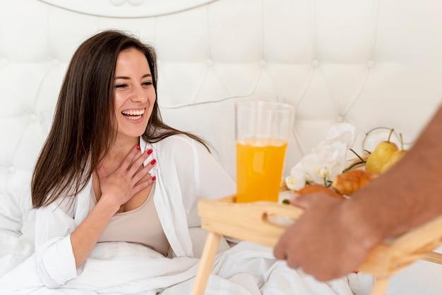 ガールフレンドのためのベッドで朝食をクローズアップ男