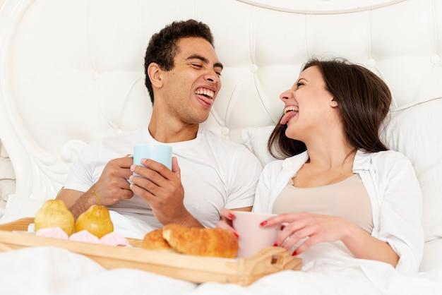 ベッドで朝食を持っているミディアムショット面白いカップル