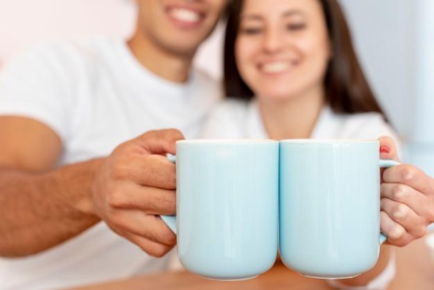 青いマグカップを保持しているクローズアップの幸せなカップル