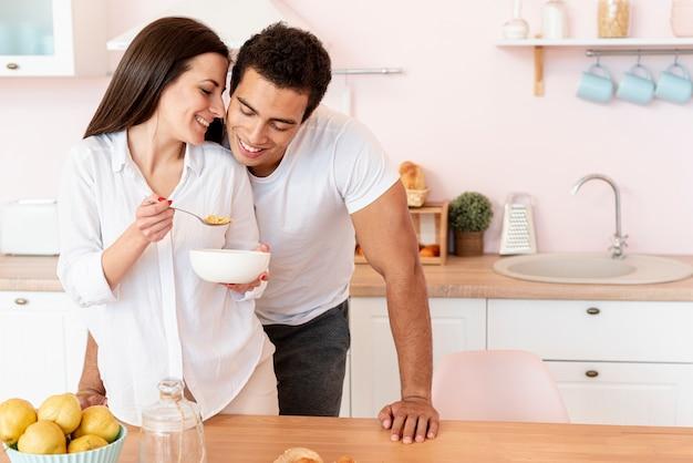 Улыбающаяся девушка среднего размера, завтракающая