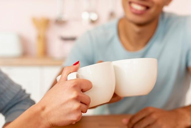 コーヒーカップとクローズアップの幸せなカップル