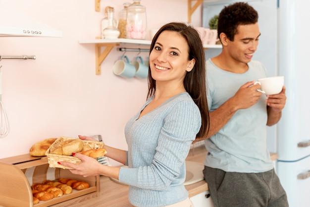 Средний выстрел женщина позирует с корзиной хлеба
