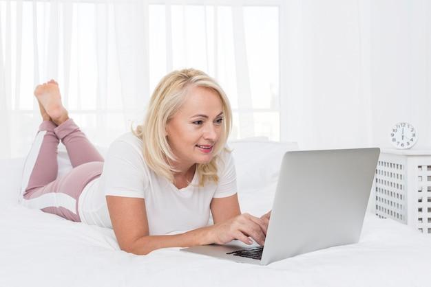 Полная съемка женщина с ноутбуком в постели