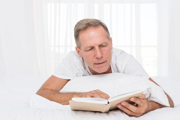 寝室で読んでいるミディアムショットの男