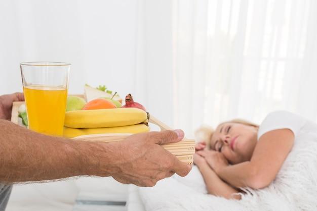 Мужчина крупным планом приносит завтрак женщине