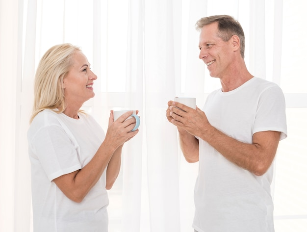 マグカップとミディアムショットの幸せなカップル