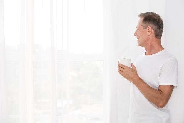 Мужчина среднего выстрела смотрит в окно