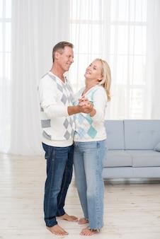 リビングルームでのフルショットの幸せなカップル