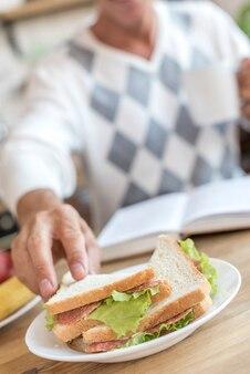 健康的なサンドイッチを食べてクローズアップ男