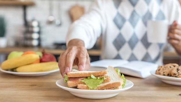 Крупным планом человек ест здоровые бутерброды на кухне