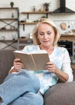 ミディアムショットの女性がソファで読書