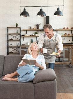 本と朝食を持つ男とミディアムショットの女性