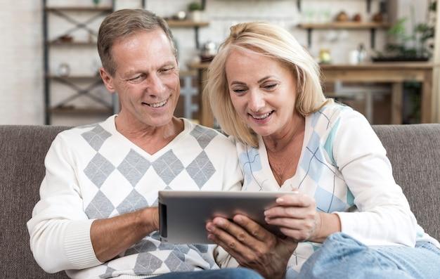 Средний снимок счастливая пара держит планшет
