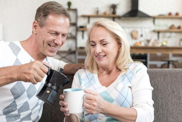 Средний выстрел мужчина наливает кофе женщине