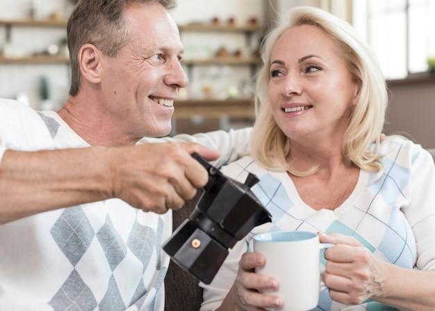 Средний снимок счастливый человек наливает кофе женщине