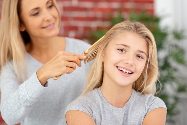 金髪の母親の娘の髪をとかす