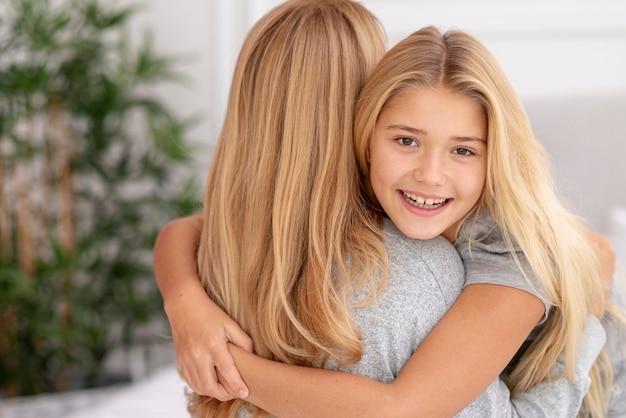 Красивая дочь, обнимая ее мать