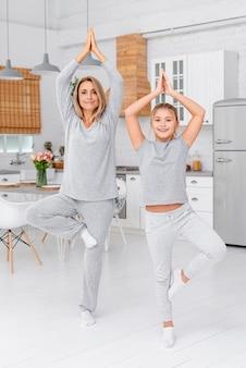 Улыбающаяся мать и дочь делают упражнения йоги