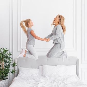 母と娘がベッドでジャンプ