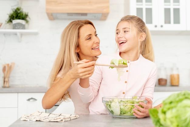 娘にサラダを提供する母