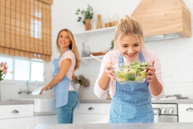サラダを見て笑顔のブロンドの女の子