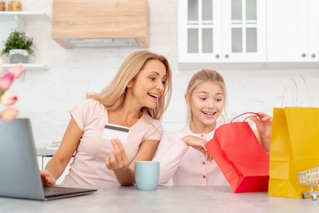クレジットカードと紙の袋で見ている娘を保持している母