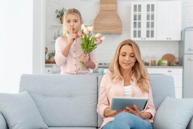Очаровательная дочь, дающая цветы своей матери