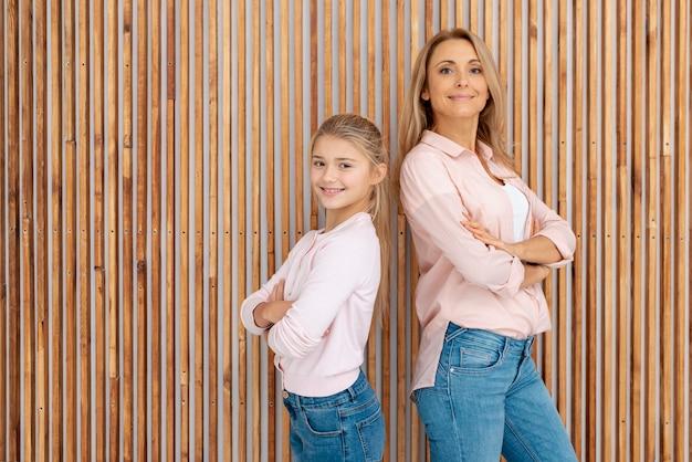 Улыбающаяся мать и дочь позирует моды