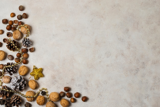 Новогодние украшения возле орехов и каштанов на столе