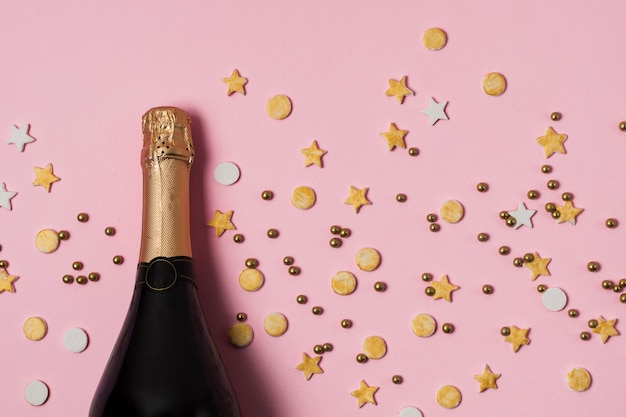 Вид сверху бутылка шампанского с конфетти