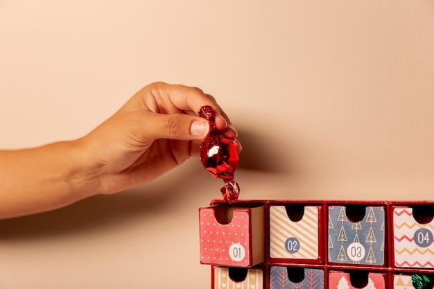Рука вставляет одну конфету в календарь появления