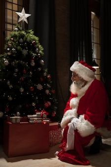 クリスマスツリーの横に座っているサンタクロース