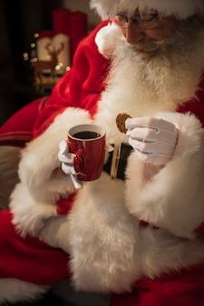 一杯のコーヒーを飲むサンタクロース
