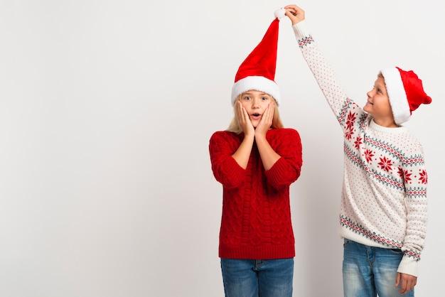 女の子サンタ帽子を引っ張る少年