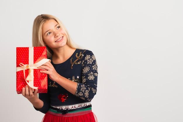 Милая девушка держит праздничный подарок