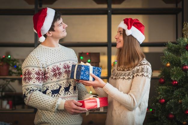 お互いに贈り物を提供するかわいいカップル