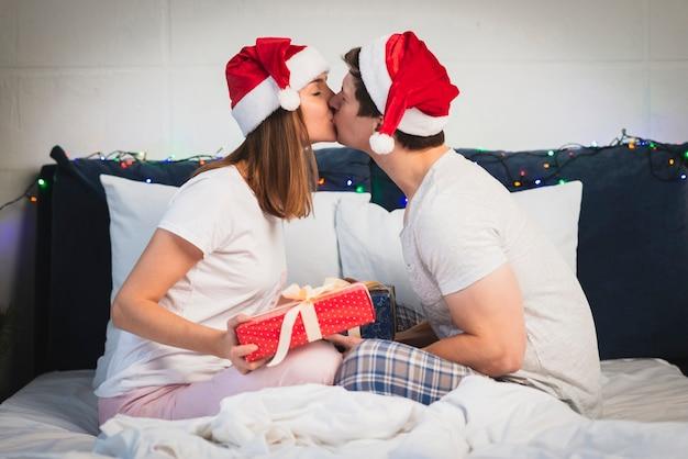 キスサンタの帽子を着ているカップル