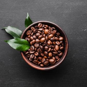 Крупный план свежих кофейных зерен с листьями