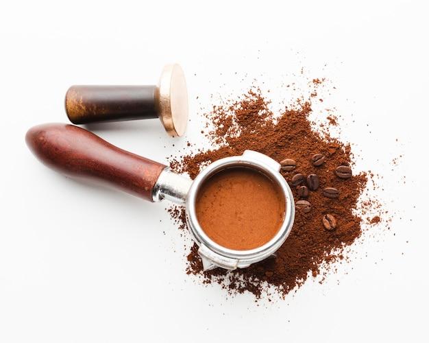 コーヒーのポルタフィルターとテーブルのタンパー