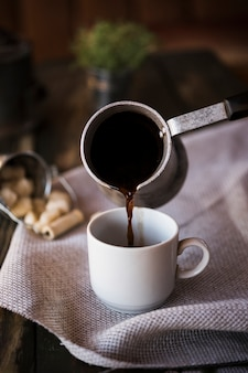 Вид спереди наливая кофе из чайника в чашку