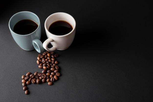 Высокий угол чашки кофе с жареными бобами
